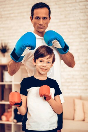 Stand in Boxing Rack. Red and Blue. Sport at Home. Warm Up in Quarter. Tablet in Hands. Boxing Gloves. Doing Sports. Man and Boy Train at Home. Child in Boxing Gloves in Apartment. Little Boy.