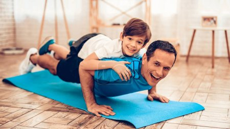 Photo for Boy Standing on Scales. Father and Son do Spotting. Sport at Home. Warm Up in Quarter. Lying on Gymnastic Mat. Dumbbells in Hands. Boxing Gloves. Doing Sports. Man and Boy Train at Home. Swing Press. - Royalty Free Image