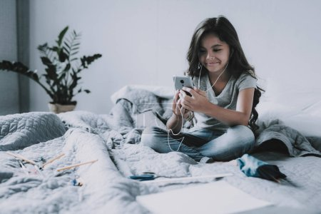 Nice Girl Listens Music in Headphones in Bedroom. Happy Smiling Little Black-Haired Child Holds Smartphone Sits on Large Gray Bed in Modern Apartment Uses White Earphones. Leisure Time Concept
