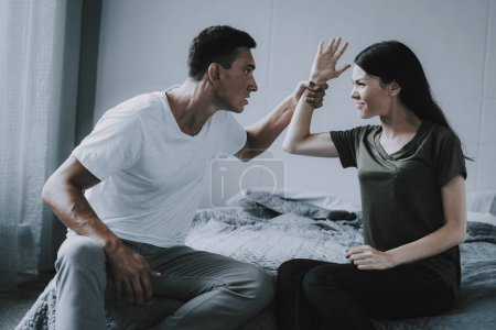 Fight and Quarrel between Woman and Man at Home. Portrait of Married Couple Sitting on Gray Bed and Arguing. Angry Husband and Wife Having Conflict in Bedroom. Family Relationship Problems Concept