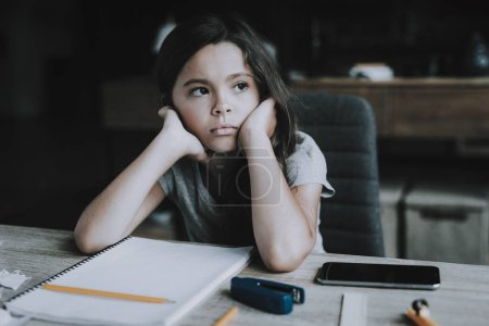 Little Girl Sits at Desk Shows Bored Expression. Portrait of Black-Haired Child Keeps Head in Hands and Looks Away with Pencil and White Notebook Lying Next on Table. Boredom and Idleness Concept
