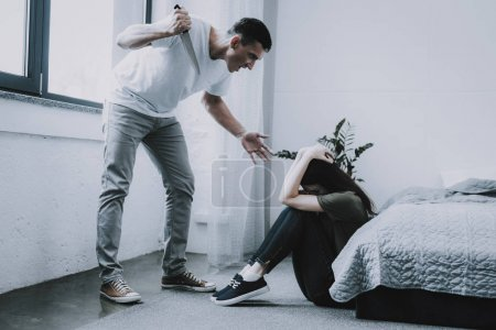Angry Man Holds Knife and Screams at Wife at Home. Woman Sitting on Floor Near Gray Bed Clasps Head Cries in Fear. Married Couple Argues in Bright Bedroom. Quarrel and Family Violence Concept