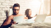 Young Business Couple Working In Bed at Night Time