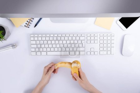 Photo for Female hands with holding banana over desktop with keyboard , top view - Royalty Free Image