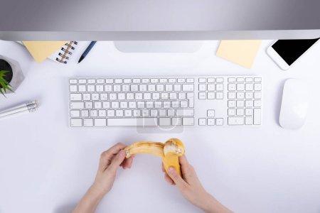Photo pour Mains féminines avec tenue banane sur le bureau avec clavier, vue de dessus - image libre de droit