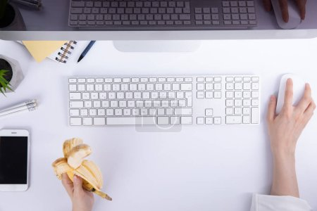 Photo for Female hands with holding banana and using computer mouse at white table, top view - Royalty Free Image