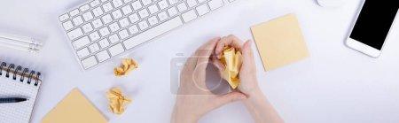 Photo pour Vue du dessus des mains féminines tenant un bloc de papier assis sur le bureau - image libre de droit
