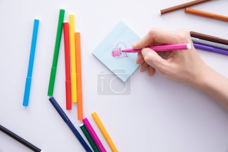 Photo for Male hand writing with felt-tip pen over paper note on table, close view - Royalty Free Image