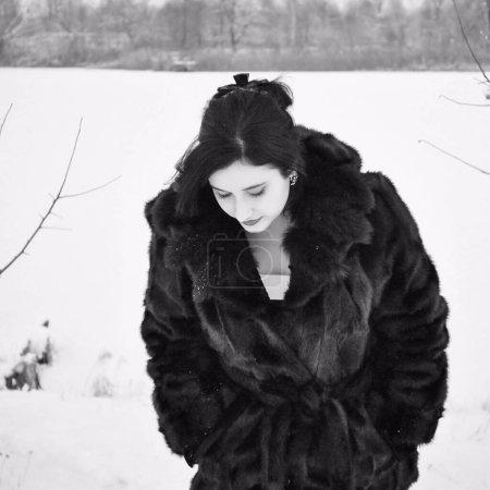 Photo pour Plus la taille belle jeune femme dans le style rétro look marcher à l'hiver usure en manteau de fourrure pas naturel. Les femmes sont de bonne humeur. Vacances d'hiver, photo noir et blanc - image libre de droit