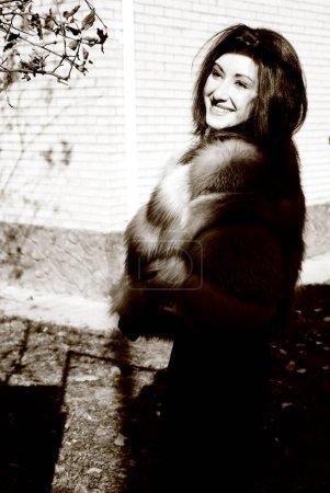 Photo pour Jeune femme en fourrures luxueuses dans la rue. Belle dame posant dans un manteau de fourrure - image libre de droit