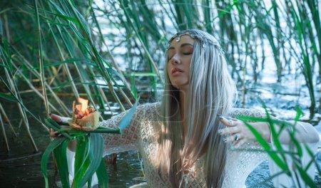 Photo pour Sirène jeune mariée en robe blanche dans le lac. Fantasy girl. Scène mystérieuse. Sorcière debout dans la rivière et pratique la sorcellerie. Conte de fées - image libre de droit
