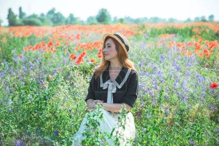 Photo pour Style vintage, fille rousse dans la prairie de coquelicots, belle nature et paysage - image libre de droit