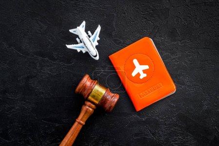 Photo pour Annulation de vol. Avion, passeport, juge marteau sur bureau noir haut vers le bas . - image libre de droit