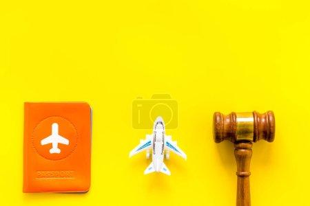 Photo pour Annulation de vol. Avion, passeport, marteau du juge sur bureau jaune haut vers le bas . - image libre de droit