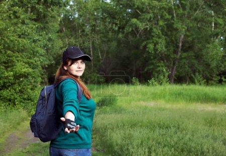 Photo pour La fille en tenue de marche regarda en arrière. Regarde dans le cadre, les arbres verts et l'herbe en arrière-plan - image libre de droit