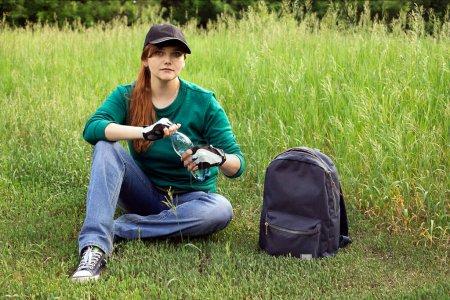 Photo pour Une fille en tenue de marche s'assoit sur l'herbe contre un paysage estival et ouvre le couvercle d'une bouteille d'eau. Il y a un sac à dos à proximité - image libre de droit