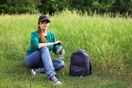 Photo pour Une fille souriante de style de vie sportif s'assoit sur l'herbe contre un paysage d'été et tient une bouteille d'eau. Il y a un sac à dos à proximité - image libre de droit