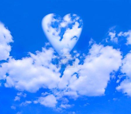 Photo pour Un cœur de nuages flottant sur d'autres nuages dans un ciel bleu vif . - image libre de droit