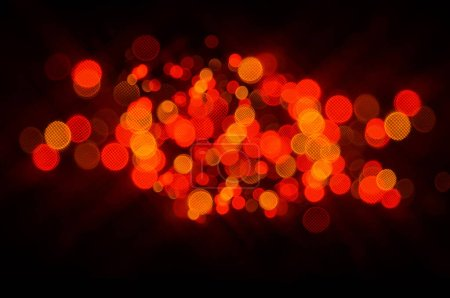 Photo for A festive bokeh design in shades of red, orange and yellow on black - Royalty Free Image