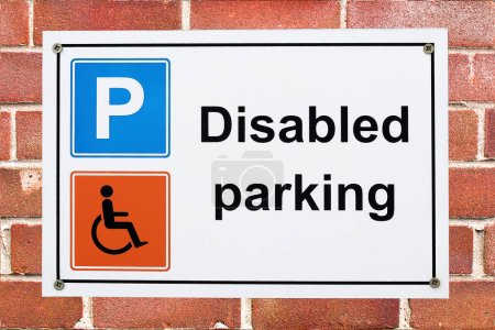 Photo for A disabled parking sign with parking and wheelchair symbols on a brick wall - Royalty Free Image