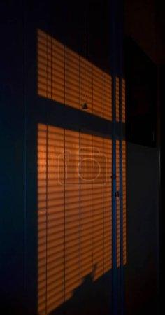 Foto de Una imagen de sombras proyectadas a través de persianas de ventana sobre una pared interior mientras el sol se pone . - Imagen libre de derechos