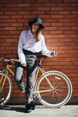 Woman posing nest to her yellow fixie bike.