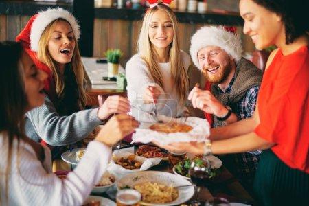 Photo pour Amis en train de dîner à la maison à la veille de Noël. Concept de vacances d'hiver. - image libre de droit