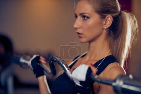 Photo pour Gros plan de femme soulevant barre de poids. Intérieur du gymnase. Concept de mode de vie sain . - image libre de droit