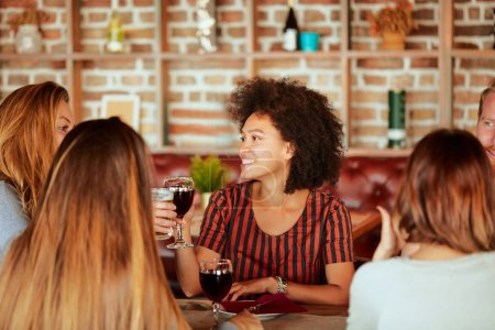 Photo for Group of friends having dinner at restaurant. Friends cheering and drinking alcohol. - Royalty Free Image