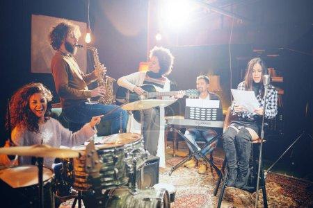 Photo pour Pratique du groupe en home studio. Femme chantant pendant que le reste du groupe joue des instruments . - image libre de droit