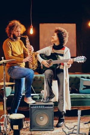 Photo pour Femme de race mixte jouant de la guitare acoustique tout en homme jouant le saxophone. Intérieur du studio à la maison. - image libre de droit