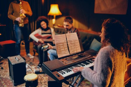 Photo for Woman playing clavier. Selective focus on woman. Home studio interior. - Royalty Free Image