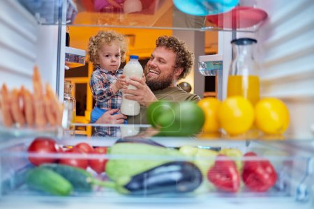 Photo for Father and son taking milk from fridge in late hours. Eating disorder concept. - Royalty Free Image