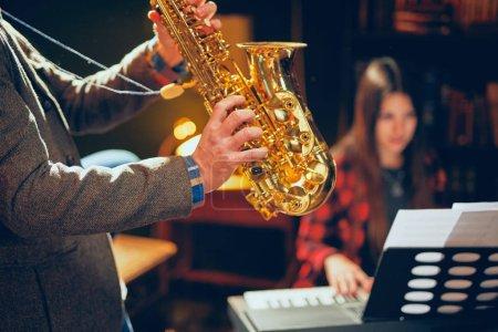 Photo pour Homme qui joue le saxophone dans home studio tout en jeune femme talentueuse jouant le clavier bien tempéré. - image libre de droit