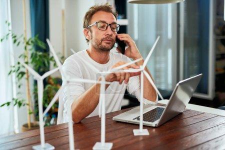 Foto de Guapo ingeniero de ecología caucásico sentado en casa y hablando por teléfono sobre el proyecto. En el escritorio hay modelos de molino de viento y portátil. Concepto de desarrollo sostenible. - Imagen libre de derechos