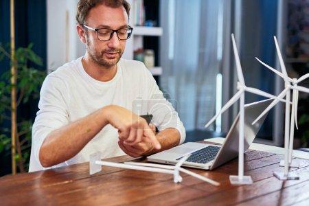 Foto de Guapo ingeniero de ecología caucásica sentado en casa, sosteniendo el teléfono inteligente y apuntando al modelo Windill. En el escritorio hay modelos de molino de viento y portátil. Concepto de desarrollo sostenible. - Imagen libre de derechos