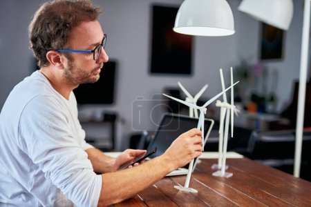 Foto de Guapo ingeniero de ecología caucásica sentado en casa y sosteniendo el modelo de molino de viento. En el escritorio hay modelos de molino de viento. Concepto de desarrollo sostenible. - Imagen libre de derechos
