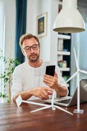 Foto de Guapo ingeniero de ecología caucásica sentado en casa y usando el teléfono inteligente. En el escritorio hay modelos de molino de viento y portátil. Concepto de desarrollo sostenible. - Imagen libre de derechos