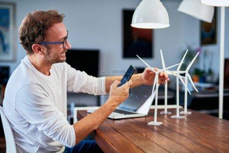 Foto de Guapo ingeniero de ecología caucásica sentado en casa y tomando fotos de la modelo de molino de viento. En el escritorio hay modelos de molino de viento. Concepto de desarrollo sostenible. - Imagen libre de derechos