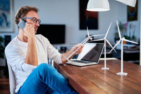 Foto de Guapo ingeniero de ecología caucásica sentado en casa, hablando por teléfono sobre el proyecto y sosteniendo el modelo de molino de viento. En el escritorio hay modelos de molino de viento. Concepto de desarrollo sostenible. - Imagen libre de derechos
