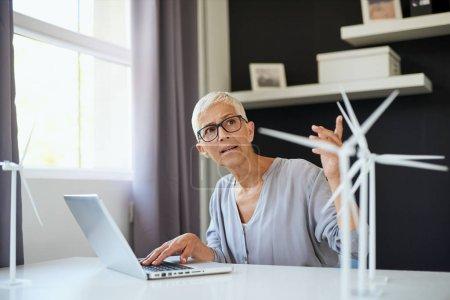 Foto de Mujer seria caucásica de la tercera edad que usa computadora portátil y habla con su colega mientras está sentada en la oficina. En el escritorio hay modelos de ordenador portátil y molino de viento. Concepto sostenible. - Imagen libre de derechos