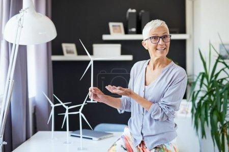 Foto de Hermosa mujer de la tercera edad sonriente caucásica apoyada en el escritorio, sosteniendo modelo de molino de viento y hablando con colega. Concepto sostenible. - Imagen libre de derechos