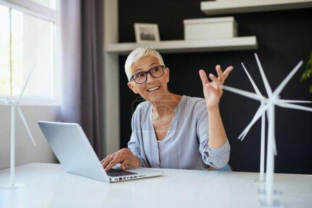 Foto de Mujer mayor del Cáucaso sonriente usando computadora portátil y hablando con su colega mientras está sentada en la oficina. En el escritorio hay modelos de ordenador portátil y molino de viento. Concepto sostenible. - Imagen libre de derechos