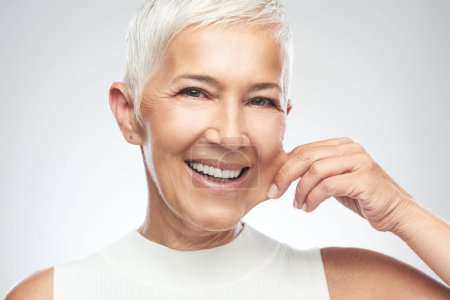 Photo for Gorgeous smiling Caucasian senior woman with short gray hair pinching her cheek. Beauty photography. - Royalty Free Image