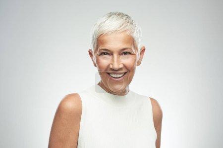 Photo pour Belle femme âgée souriante aux cheveux gris courts posant devant un fond gris. Photographie beauté . - image libre de droit