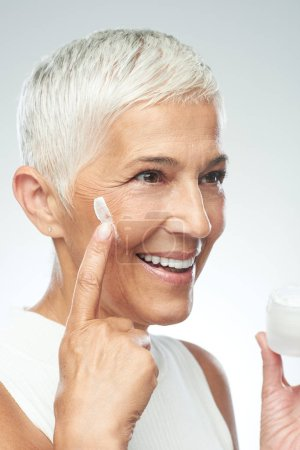 Photo pour Superbe femme âgée caucasienne souriante qui essaie une nouvelle crème anti-âge. Photographie beauté . - image libre de droit