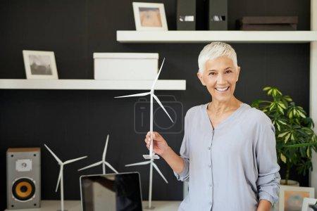 Foto de Hermosa mujer de la tercera edad sonriente caucásica de pie en el cargo y sosteniendo modelo de molino de viento. Start up business concept. - Imagen libre de derechos
