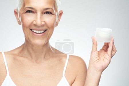 Foto de Hermosa mujer de la tercera edad sonriente caucásica probando nueva crema anti edad y mirando a la cámara. Fotografía de belleza. - Imagen libre de derechos