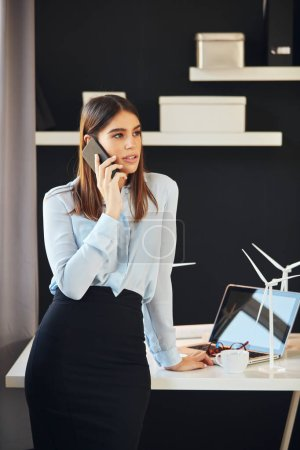 Foto de Attractive business woman dressed in formal wear standing in office, using smart phone. Sobre la mesa están los modelos de molinos de viento y el portátil. Concepto de desarrollo sostenible. - Imagen libre de derechos