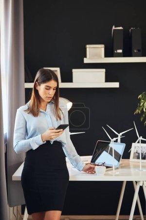 Foto de Atractiva mujer de negocios vestida con ropa formal de pie en la oficina, usando el teléfono inteligente y sosteniendo una taza de café. Sobre la mesa están los modelos de molino de viento y portátil. Concepto de desarrollo sostenible. - Imagen libre de derechos